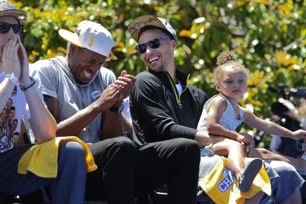 Stephen Curry, holding his daughter Riley, laughs with Andre Iguodala during the Golden State Warriors Victory Parade and Rally in Oakland, on Friday, June 19, 2015.   (Christopher Chung/ The Press Democrat)